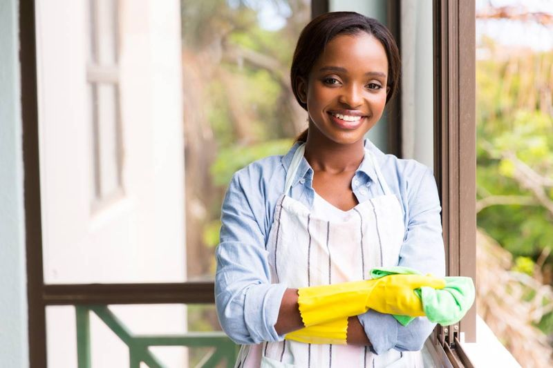 beautiful African American housekeeper cleaning the window | jobs in Canada