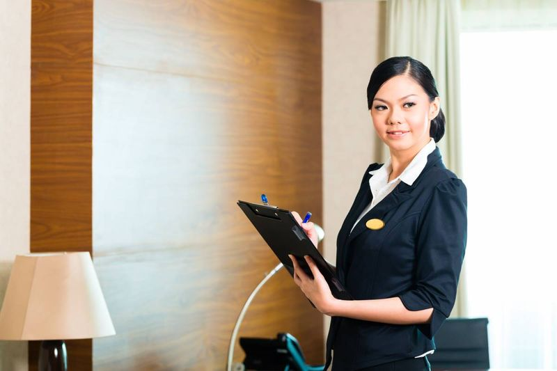beautiful Asian woman holding clipboard executive housekeeper in hotel | jobs in Canada