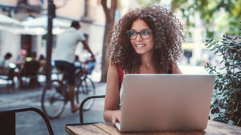 beautiful-female-freelancer-sitting-at-street-cafe-table-with-laptop   family sponsorship Canada