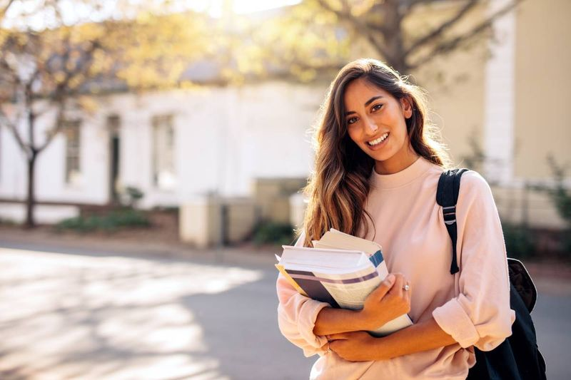 smiling beautiful female student holding books | study in Canada