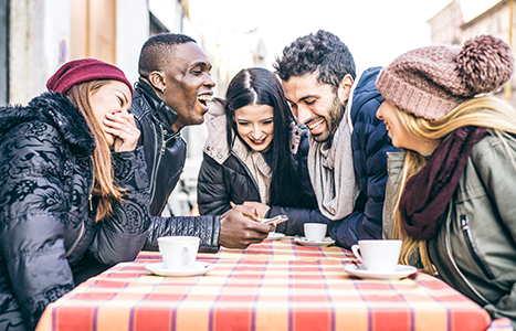 group of young people laughing over coffee