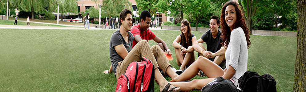 university students sitting on campus grounds outside