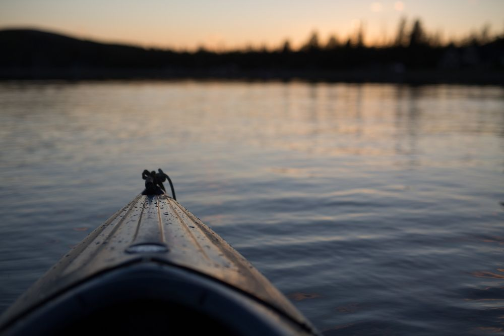 canoe on lake waters at sunset