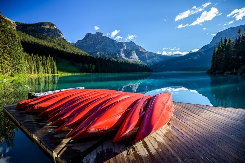 red canoes in front of lake and canadian rockies