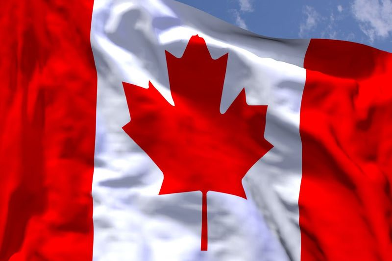 Canadian flag blowing in blue sky