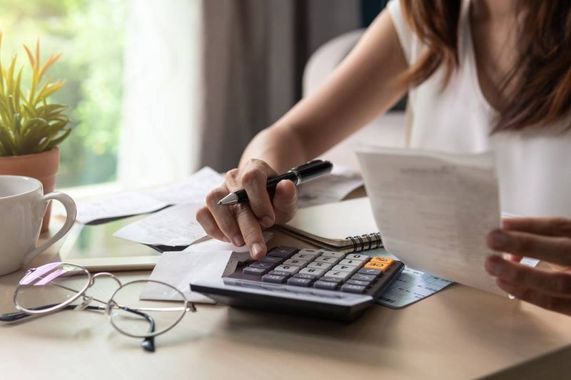 women calculating cost of living in Canada on calculator with bills