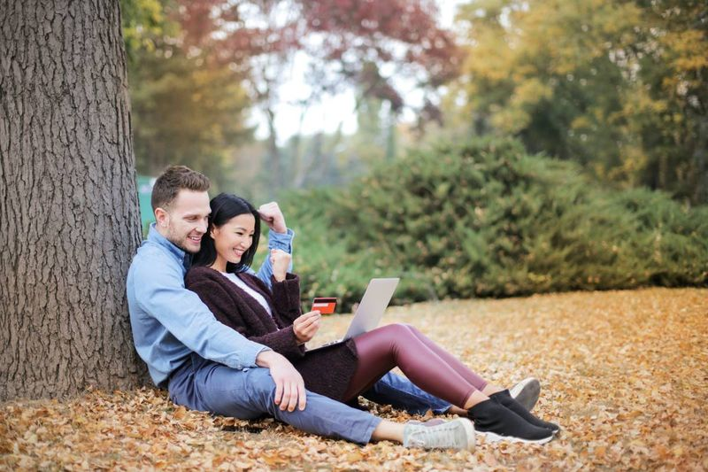 couple sitting beside tree applying to immigrate to Canada on laptop