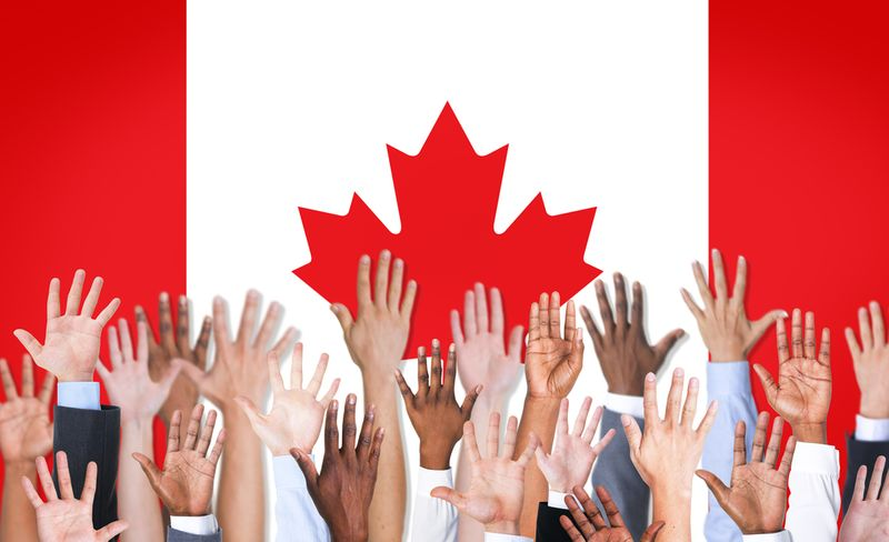hands reaching up in front of Canadian flag | permanent residence Canada