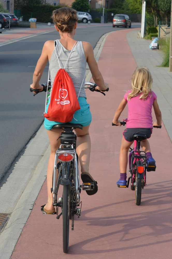 mother and daughter cycling on city path