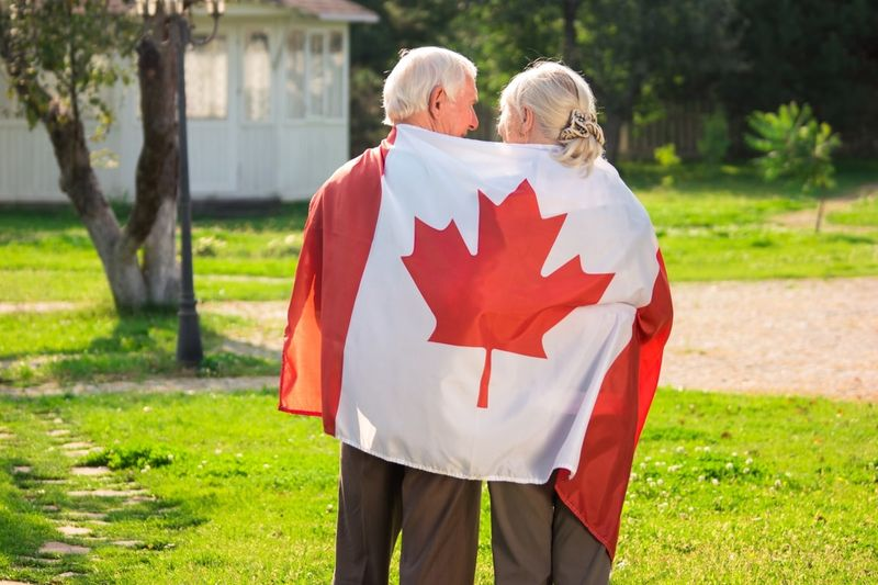 elderly couple hugging with the canadian flag