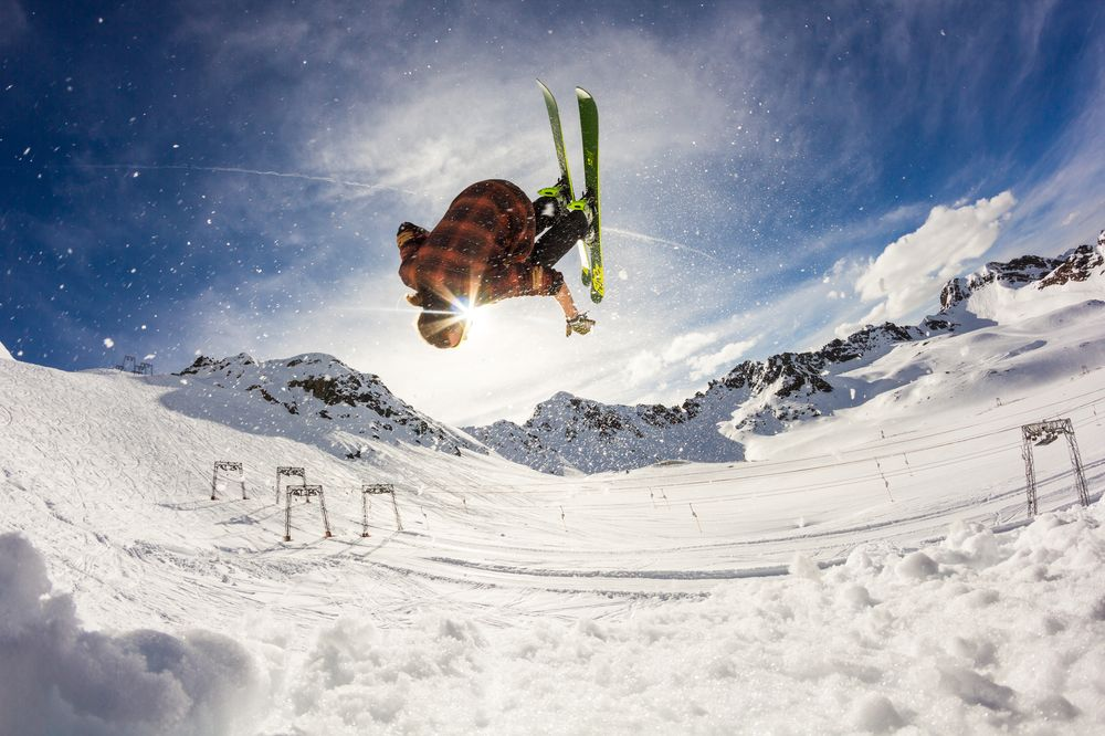 skier doing flip on snowy mountain peaks