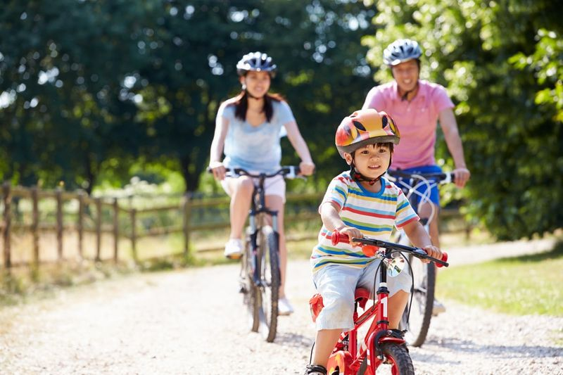 family cycling together in the countryside
