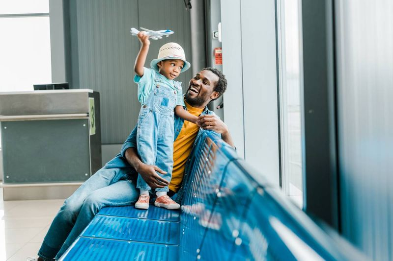 father sitting with child at airport about to immigrate to Canada