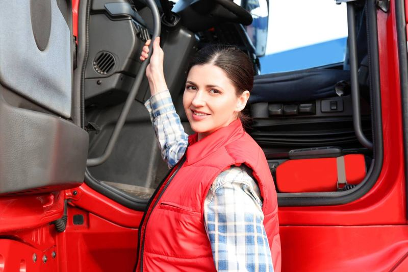 female truck driver in front of red truck | immigrate to Canada
