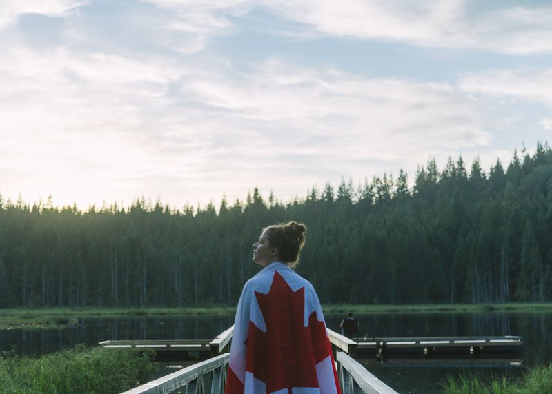 Girl proudly shows her Canadian PR status wearing a Canadian flag.
