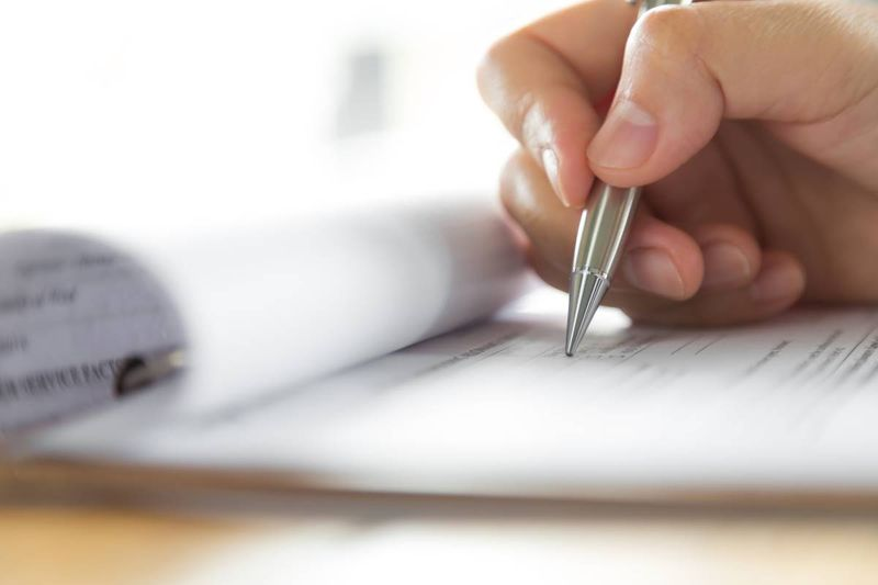 hand using pen to complete application form   immigrate to Canada