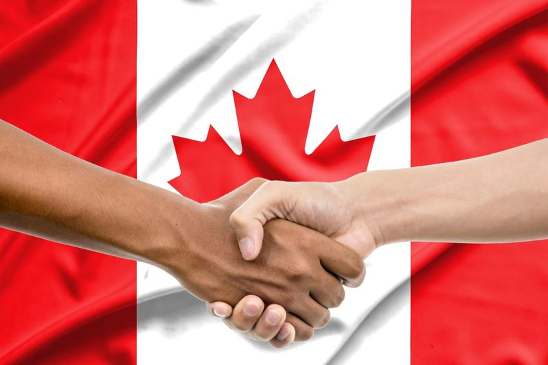 shaking hands in front of Canadian flag