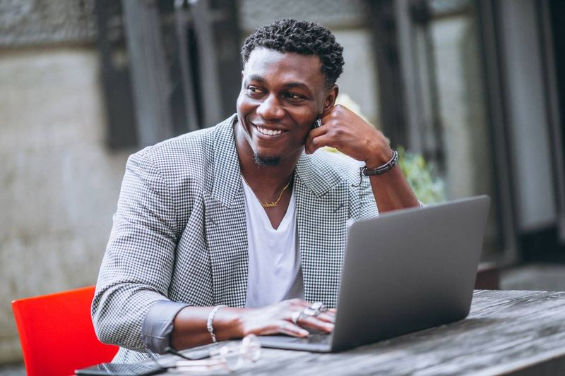 happy African American man using laptop | Apply for Canada visa from the Ivory Coast