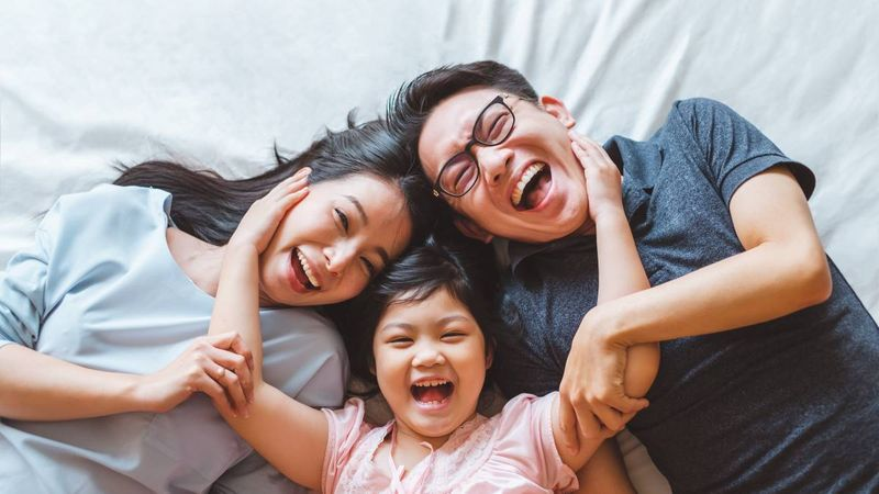 happy-asian-family-laying-on-bed-top-view | family sponsorship Canada