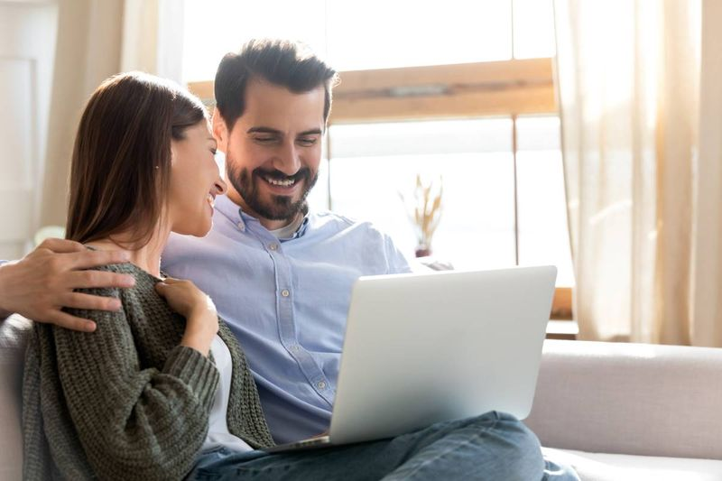 happy-couple-sitting-on-couch-with-laptop | move to Canada form the UK
