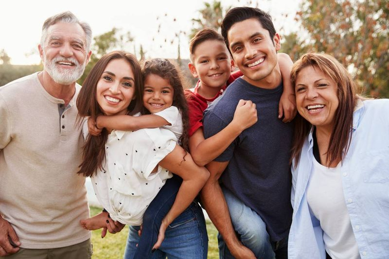 happy Latino family in park with grandparents | family sponsorship Canada