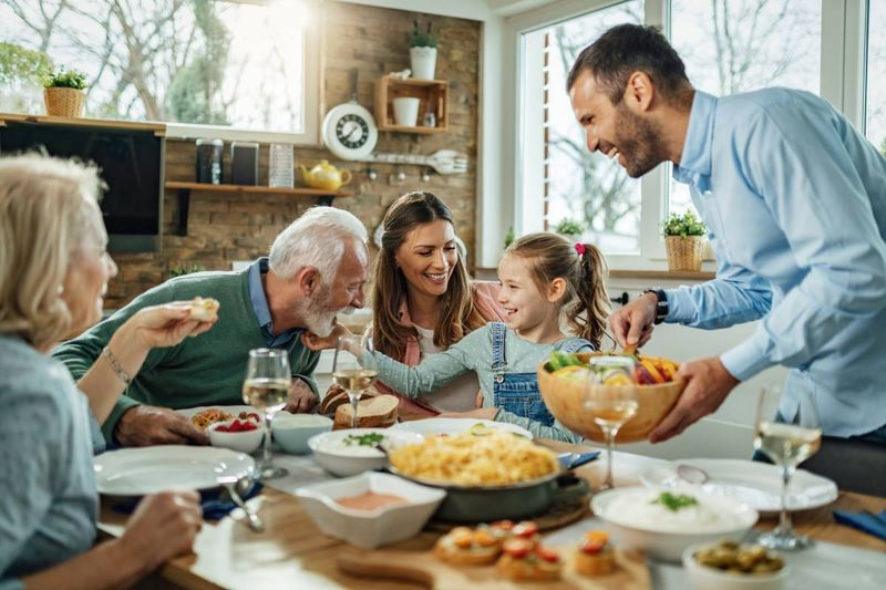 happy multi-generation family at dinner table | family sponsorship Canada
