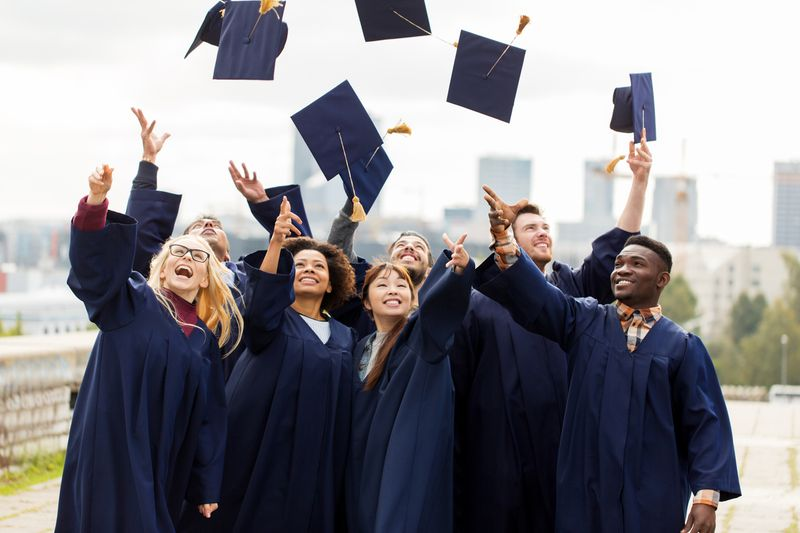 happy multicultural graduates throwing caps in air | Post-Graduation Work Program