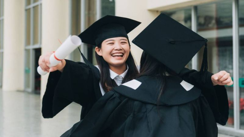 Chinese graduate happy and hugging a friend