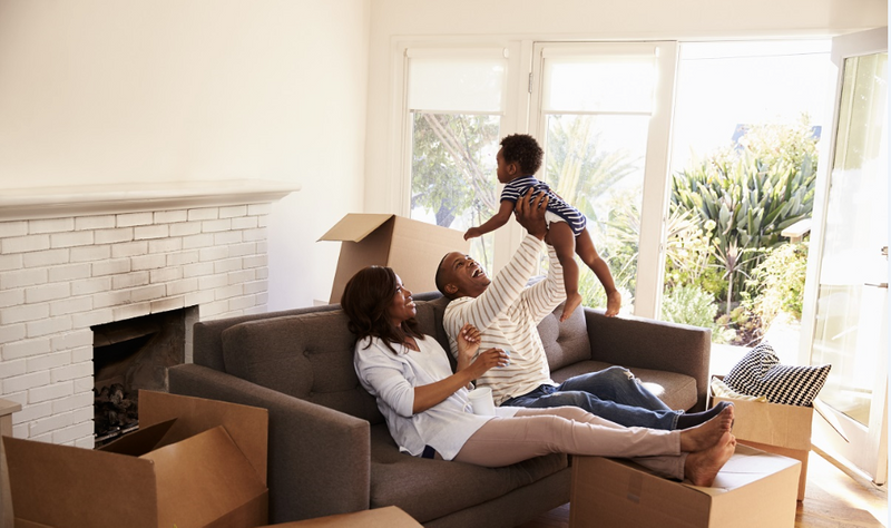 Parents playing with their baby in a new house | Family benefits in Canada