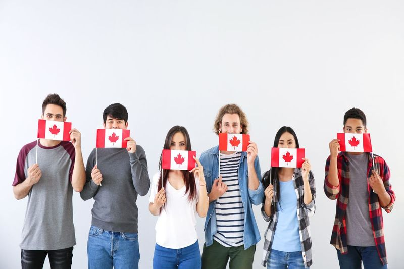 international students holding Canadian flags | study in Canada