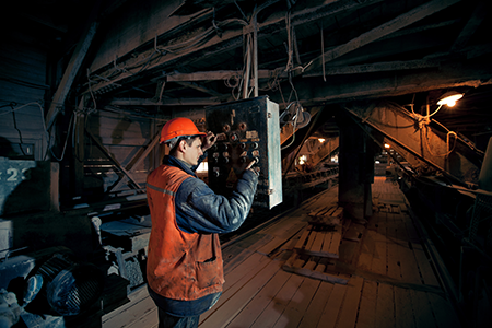 A mine worker operating heavy duty machine