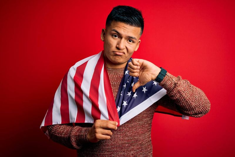 Latin American man holding American flag with thumbs down | immigrate to Canada in 2020
