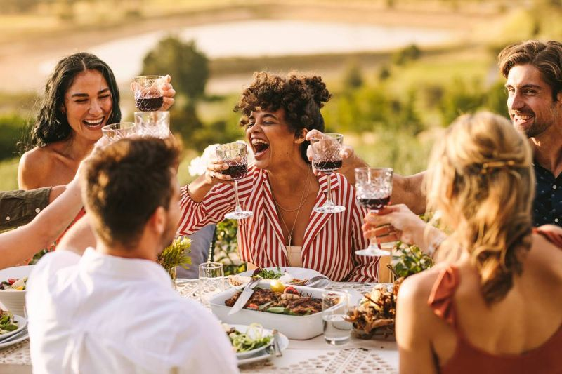 multi-ethnic people eating and drinking wine on a wine farm | how to apply for a Canadian visa from Italy