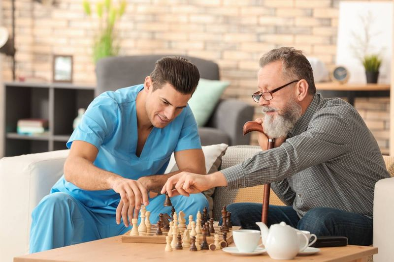 male-caregiver-playing-chess-with-older-man | work in Canada