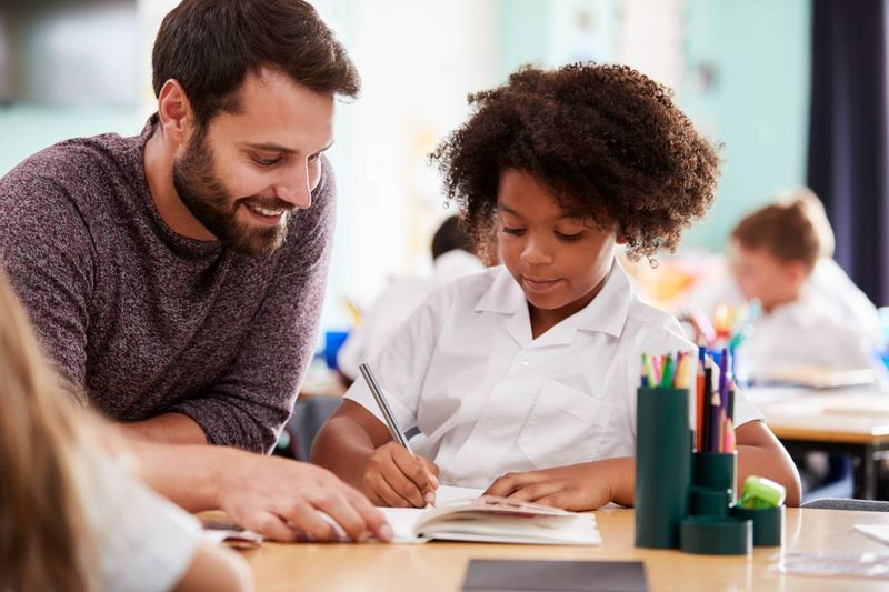 male-elementary-teacher-helping-student-with-school-work   Canada Express Entry