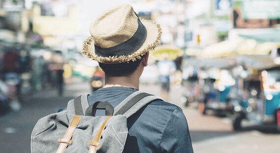 A man wearing a fedora hat walking through busy street