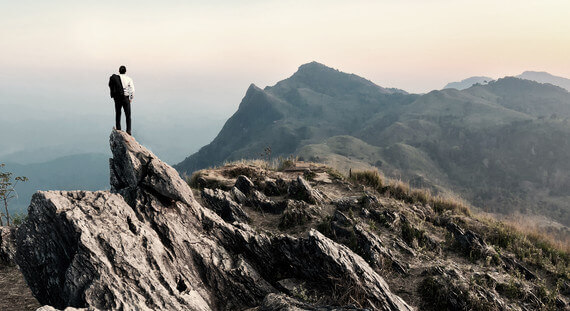 A man stands on a ledge looking over mountain terrain