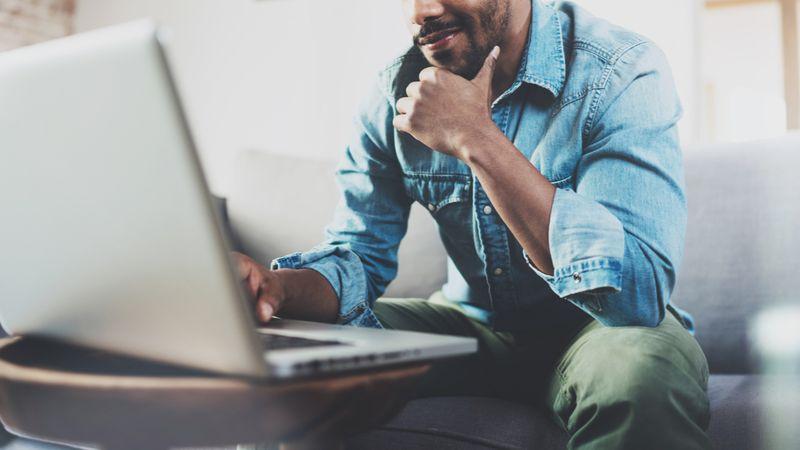 man smiling working on laptop   freelancer   IEC Working Holiday Program