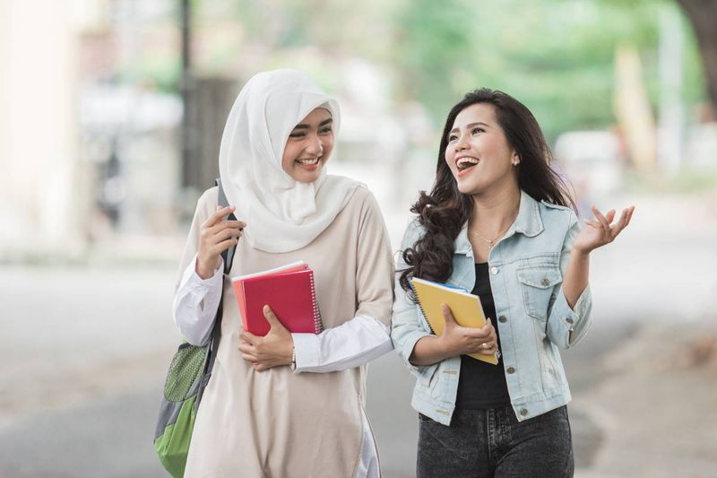Female Muslim and Asian students smiling | immigrate to Canada