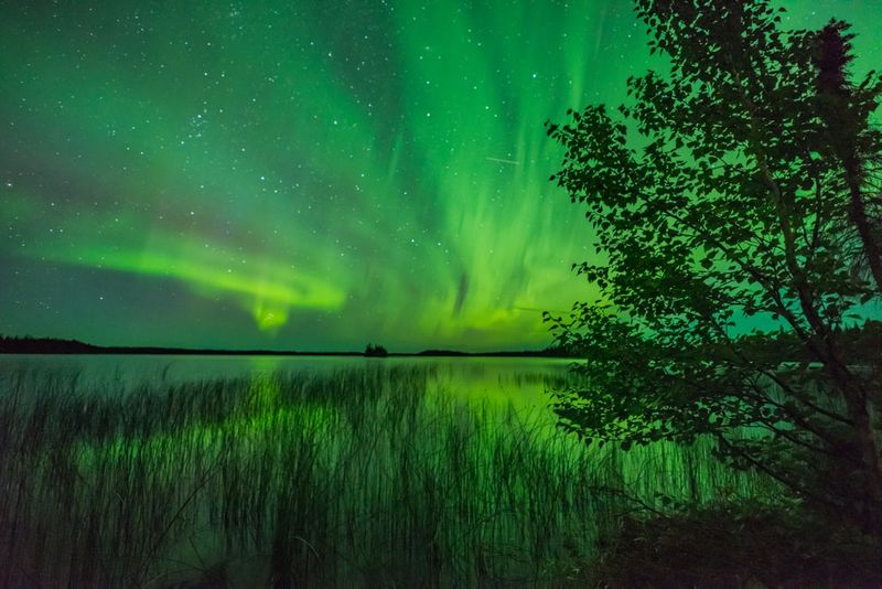 Northern lights over lake in Manitoba Canada | migrate to Canada