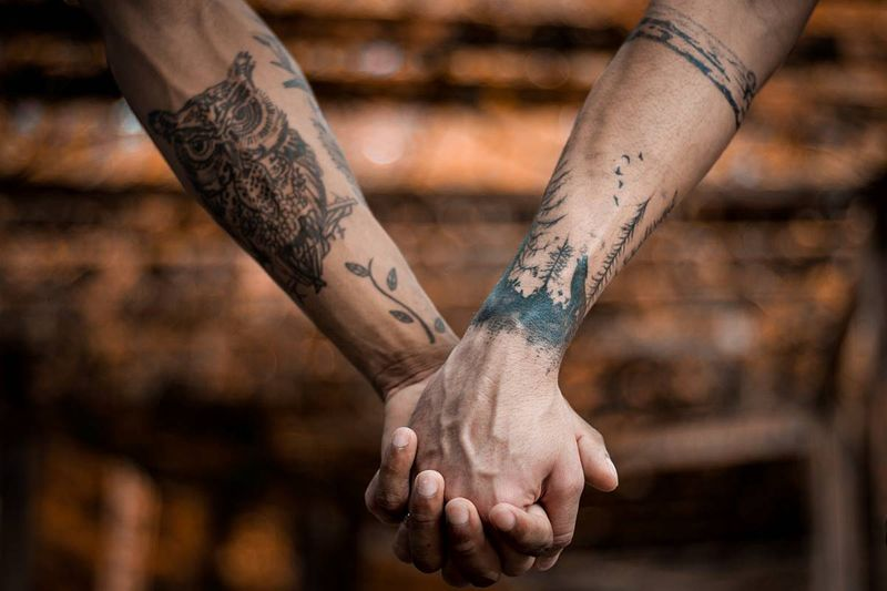 same-sex couple holding hands tattoos in canada