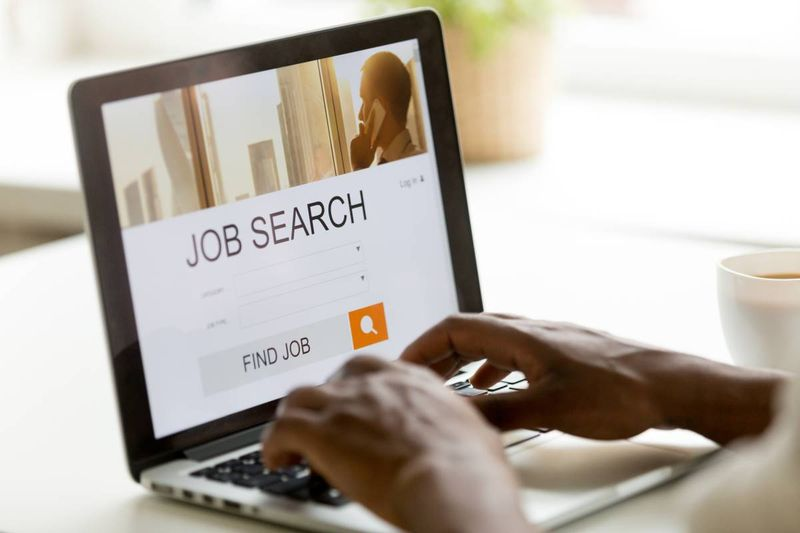 person typing on laptop job search online   jobs in Canada