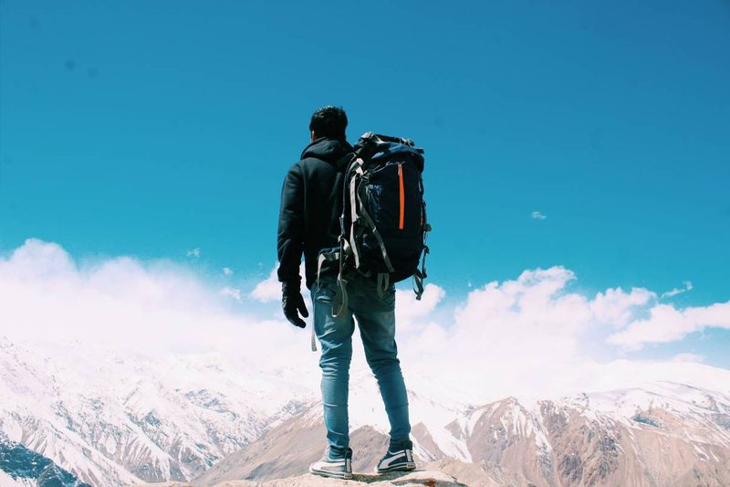 man standing on mountain with backpack | working holiday visa to Canada