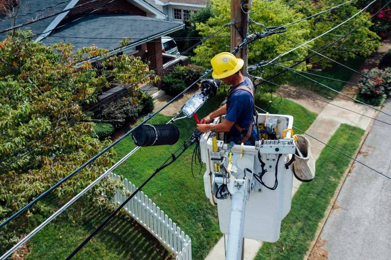 electrician fixing electric wires in front of house