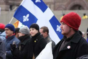 group of quebec workers marching in the street carrying quebec flags