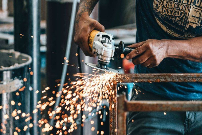 semi-skilled worker using grinder in Canadian workshop
