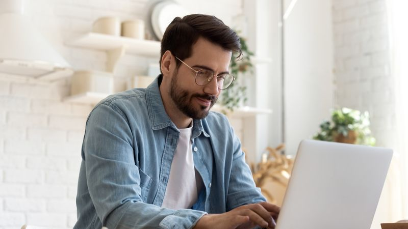 Focused young man wearing glasses using laptop,