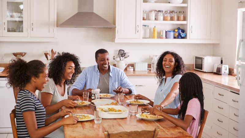 Family With Teenage Children Eating Meal In Kitchen