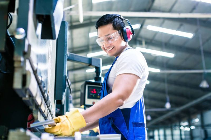 smiling Asian man working as machinist in factory | immigrate to Canada