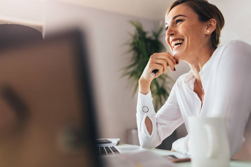 smiling beautiful professional woman sitting at desk | business immigration to Canada